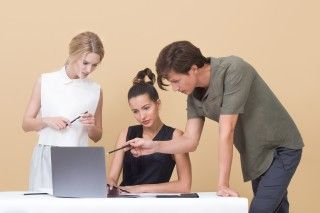 Man pointing to grey computer, with two women next to him.